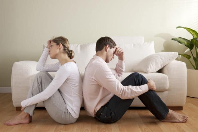 Ein Paar hat einen Beziehungsstreit und sitzt Rücken an Rücken am Boden