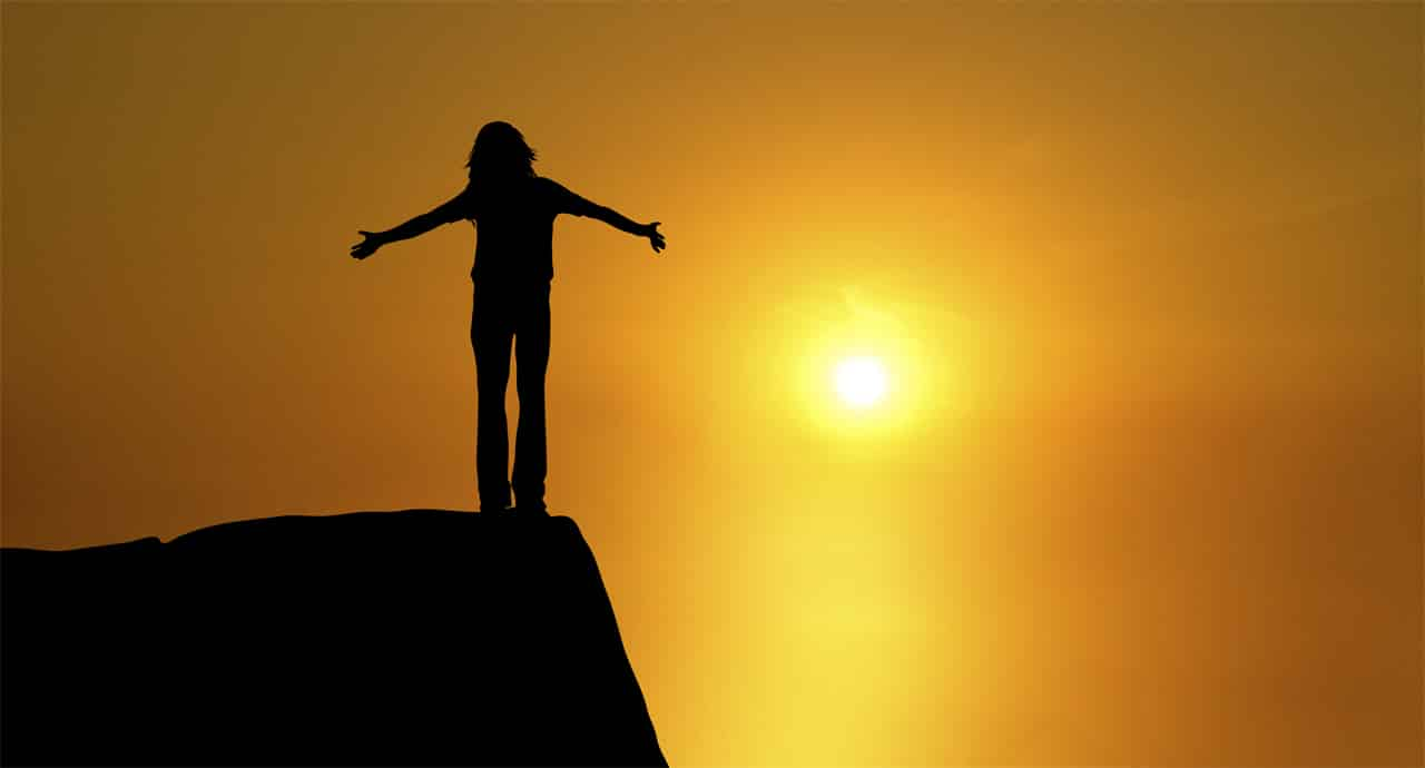 Ein Mensch steht auf einer Bergspitze im Sonnenuntergang