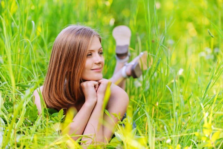 Eine glückliche Frau liegt im Sommer im Gras