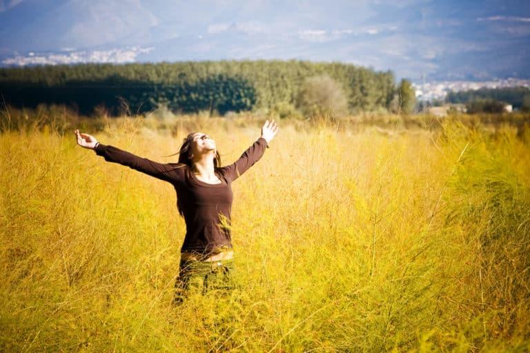 Eine freudige Frau im Weizenfeld mit hochgestreckten Armen