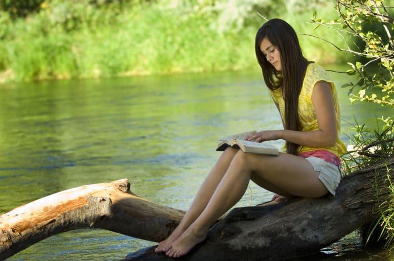 Eine Frau sitzt auf einem Baum am See und liest ein Buch