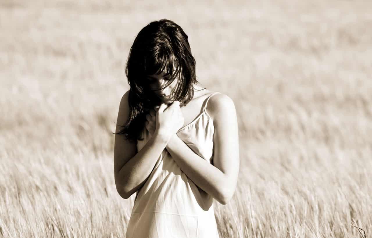 Eine Frau zeigt Emotionen und steht in einem Weizenfeld